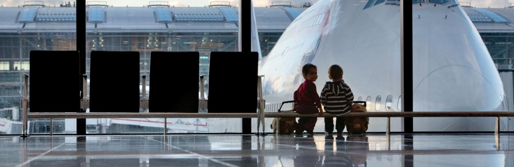 Kids looking outside airport window
